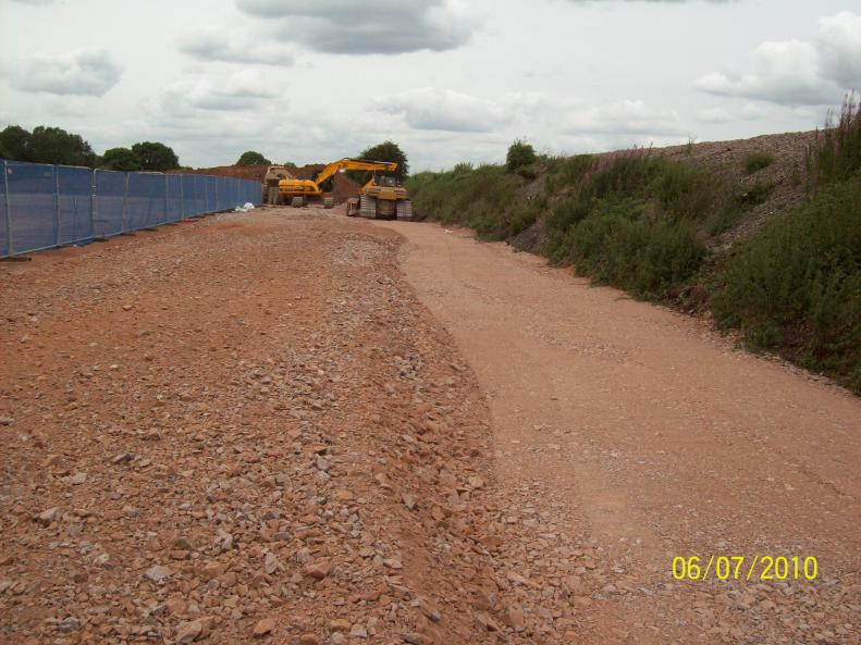 Stone being placed and compacted along the bottom of the embankment