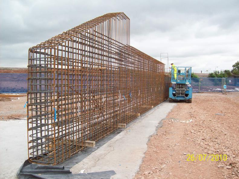 Steel cage being fixed - Note the timbers being used to stop the cage falling over.