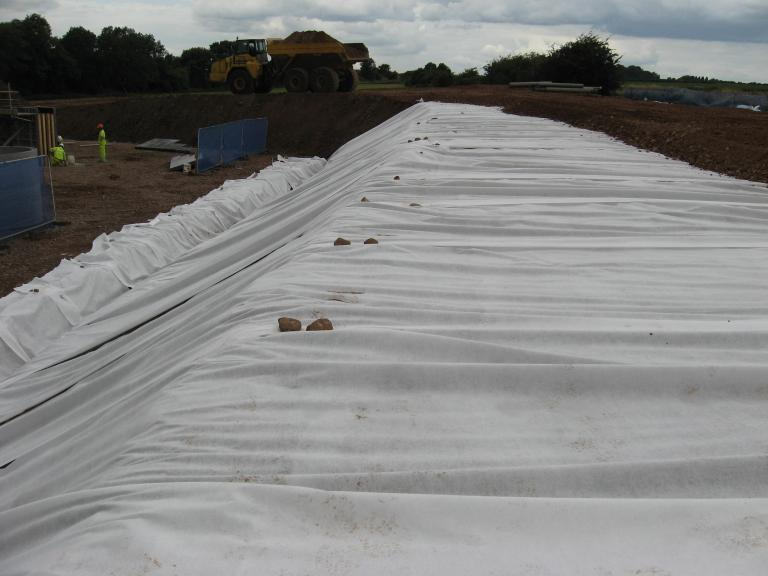 6F5 being placed on the top of the platform - geotextile rolled down the embankment to give erosion control.