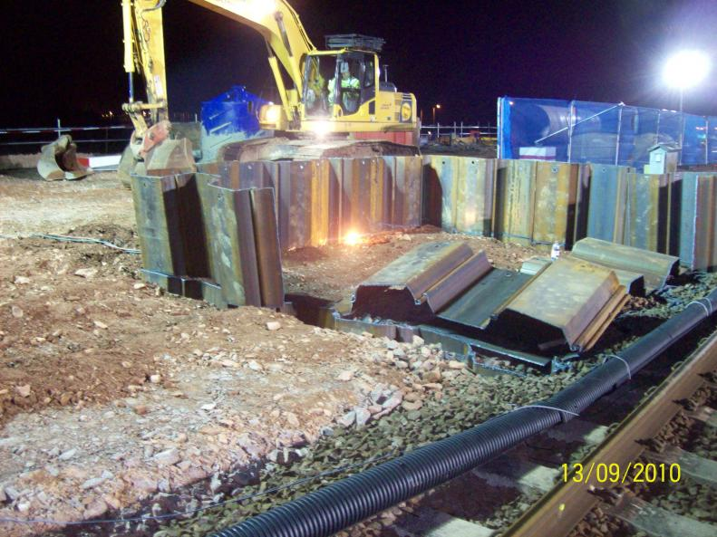 Top section of sheet piles being cut down.