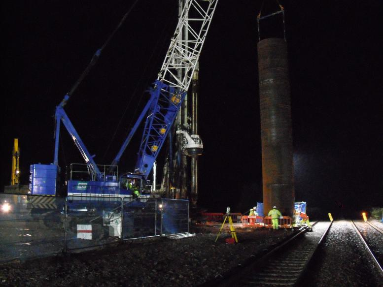 Crane lifting the steel casing into the pre-bore.