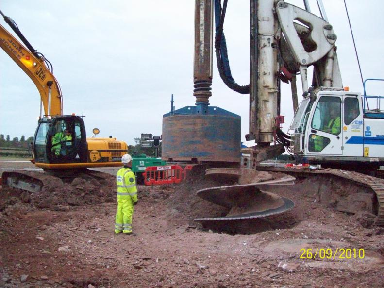 Pile rig drilling and cleaning out the bottom of the piles.