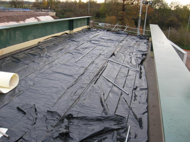 Concrete covered with polythene post pour with frost blanket placed over the polythene.