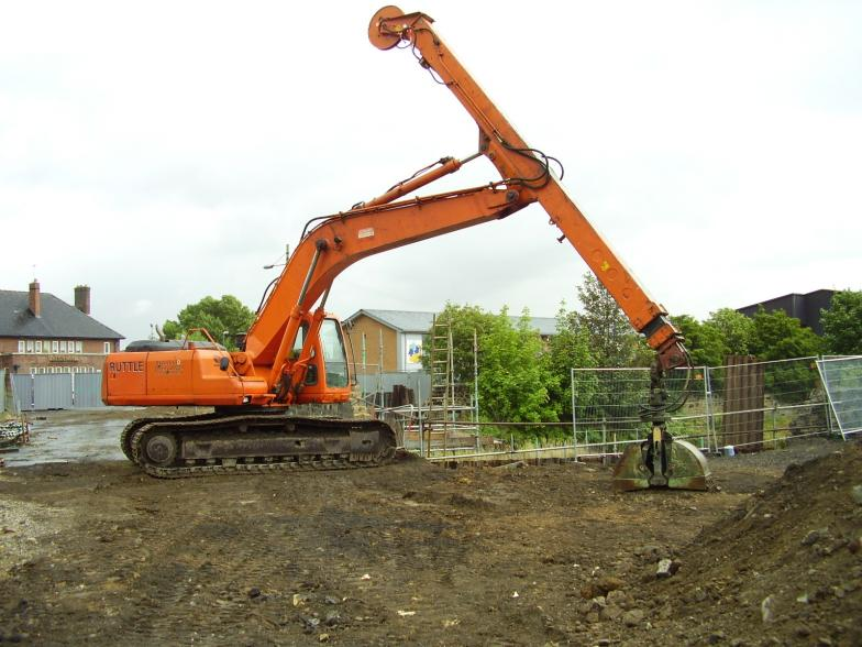 Excavator with grab on site to dig out down the back of the abutment.
