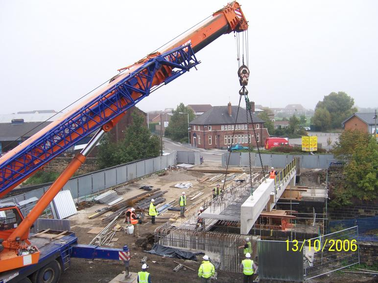 Concrete parapet unit being installed during normal working.