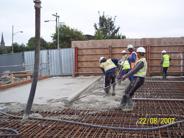 Concrete being placed and levelled using a roller screed.
