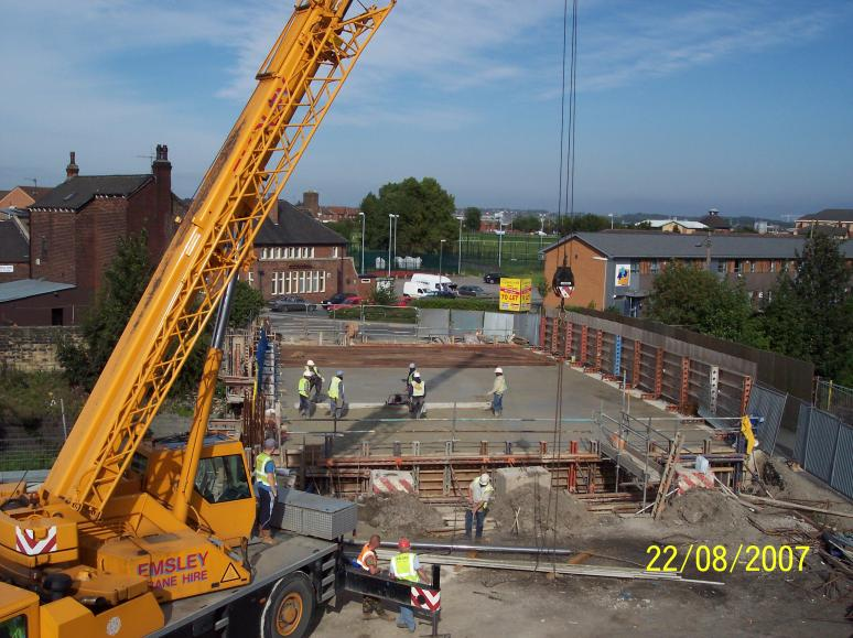 Crane being used to lift screed rails and screed of the deck at the end of the pour.