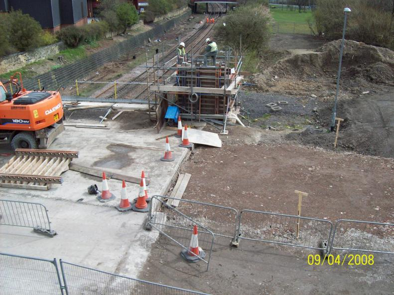 Works progressing on the South East Pillaster - concrete being placed by skip and excavator.