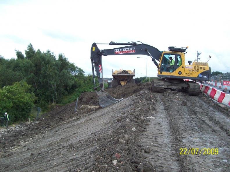 Excavator  creating the embankment over the infilled deck.