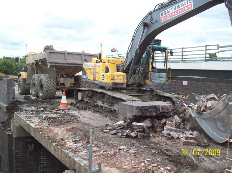 Excavator on the deck clearing parapet.
