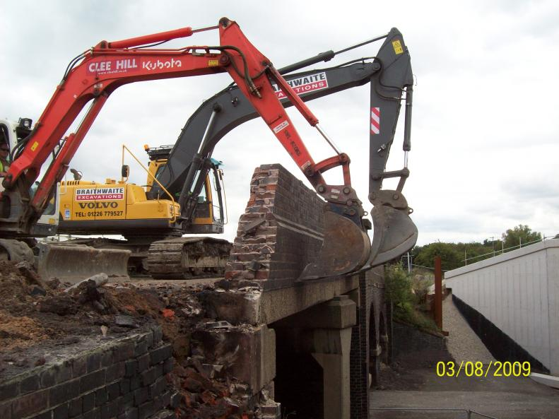 Excavators working together to pull in the parapets