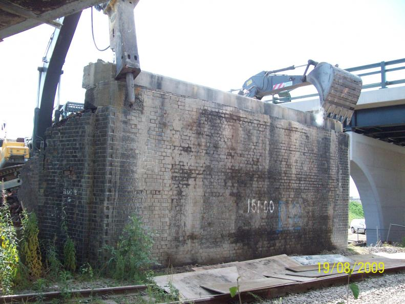 Concrete capping beam being pulled off by two excavators