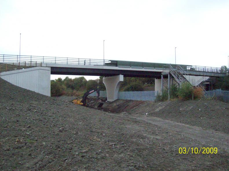 Pallasade fence being installed between the track and the canal.